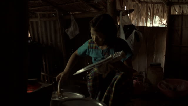 f/s burmese teenage girl cooking in a traditional house - myanmar stock-videos und b-roll-filmmaterial