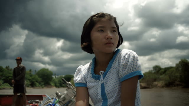m/s burmese teenage girl in a motorboat, clouds, low angle - myanmar stock videos & royalty-free footage