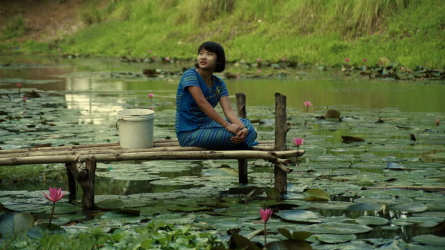 L/S Burmese teenage girl in a pond to collect water, traditional dress