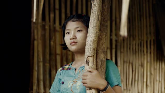 M/S Burmese teenage girl in the door of her house