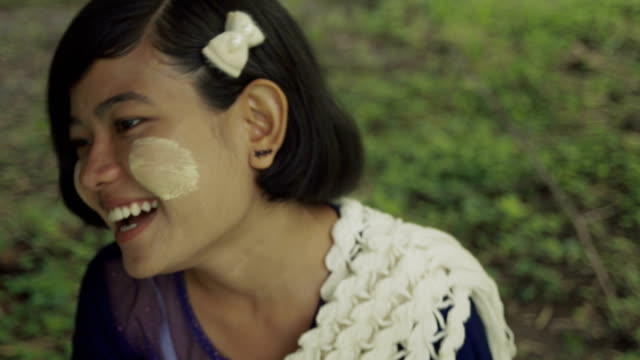 vidéos et rushes de m/s burmese teenage girl talking and laughing in a park, traditional dress - châle