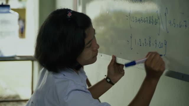 vídeos y material grabado en eventos de stock de m/s burmese teenage girl writing in a whiteboard, class - sólo una adolescente