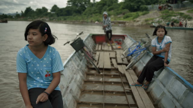 f/s burmese teenage girls sailing a river in motorboat - myanmar stock-videos und b-roll-filmmaterial