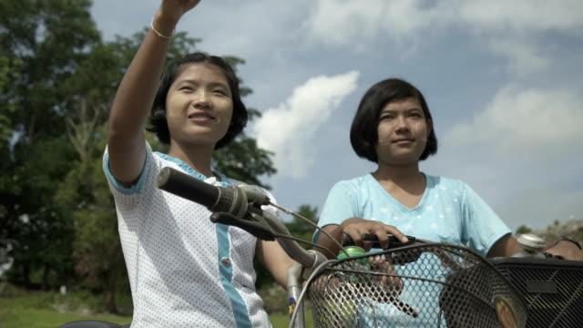 m/s burmese teenage girls with bicycles - ミャンマー点の映像素材/bロール