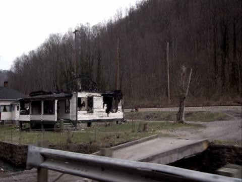 burned and derelict houses overlook a rural highway in appalachia. - appalachen region stock-videos und b-roll-filmmaterial