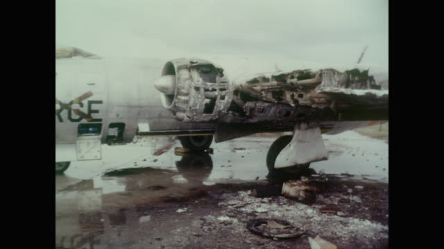 burned out trucks and damaged planes make up the bulk of destruction at bien hoa air base after an attack by the vietcong damaged but still standing... - ベトコン点の映像素材/bロール