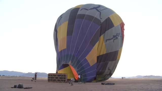 vídeos de stock e filmes b-roll de a burner blows flames into a hot air balloon in the desert. - soprar