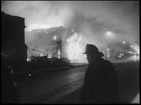 vidéos et rushes de b/w 1967 burning building after race riots at night / silhouette fireman walking in foreground / detroit - 1967