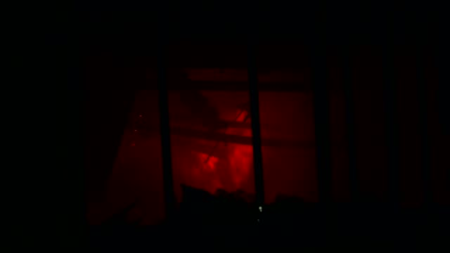 Burning building at night, view through the window