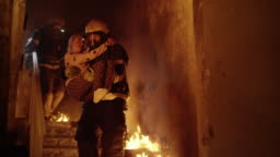 Burning Building. Group Of Firemen Descend on Burning Stairs. One Fireman Holds Saved Girl in His Arms.