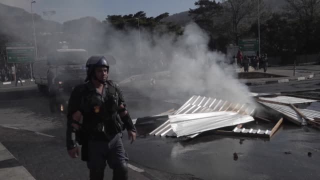 Burning building material blocks the road entrance to Imizamo Yethu in Hout Bay on the outskirts of Cape Town after clashes between residents and...