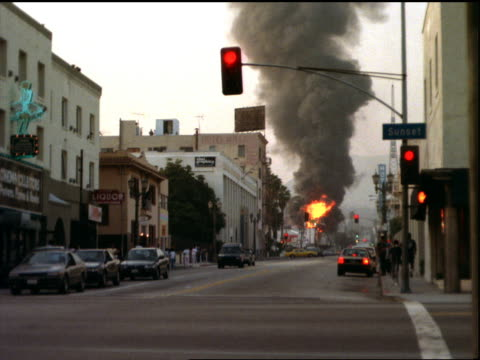 burning building on city street with traffic / los angeles riots - anno 1992 video stock e b–roll