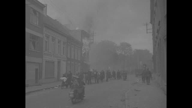 VS burning buildings in small Belgian town / VS refugees on foot bicycles pass burning building / VS structures blaze / VS refugees in wagons on...