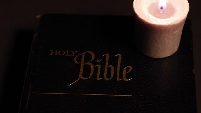 vidéos et rushes de bougie allumée sur une bible - couverture de livre