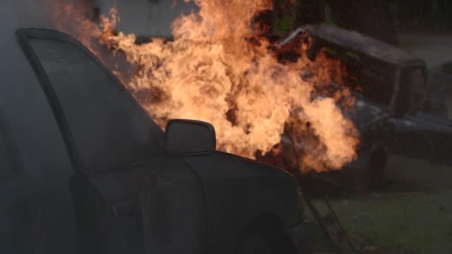 vidéos et rushes de voiture brûlante sur la route dans la nuit. - épave