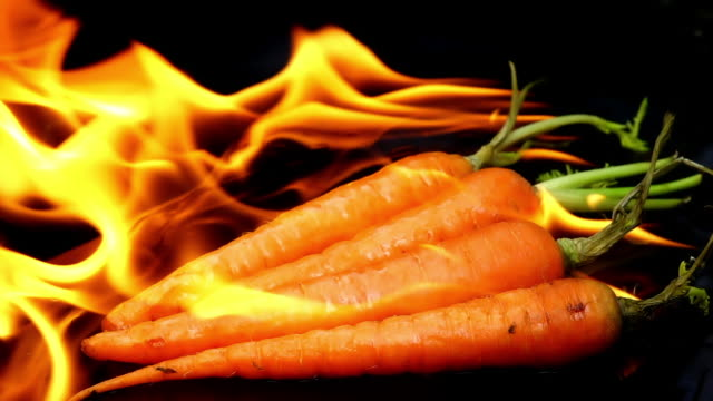 burning carrot on black background slow motion - carrot stock videos & royalty-free footage