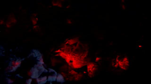 burning coals and ash fill a fireplace. - 石炭点の映像素材/bロール