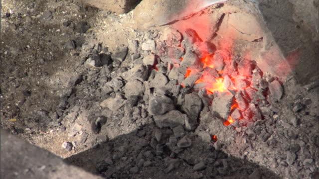 CU TU Burning hot coals and woman cranking wheel to fuel fire, Pune, Maharashtra, India