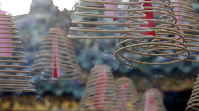 cu pan burning incense coils outside of temple / singapore - tempel stock-videos und b-roll-filmmaterial