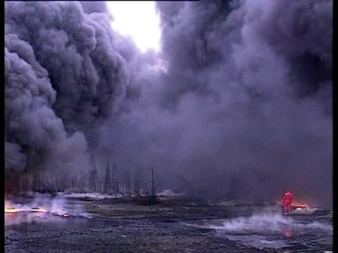 burning oil and large plumes of black smoke with greenpeace man in boiler suit to right of shot, komi region, russia. - mid distance stock videos & royalty-free footage