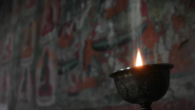 burning oil lamp inside thiksay monastery and it's murals depicting life of buddha in ladakh, jammu and kashmir, india - religion stock videos & royalty-free footage