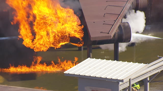 cu aerial ts burning refinery simulator with training crew in brayton fire training field / college station, texas, united states - firefighter stock videos & royalty-free footage