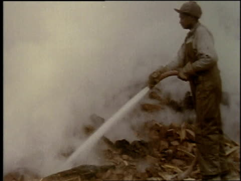 vídeos y material grabado en eventos de stock de 1957 montage burning ruins, smoke rising as man is hosing debris / united states - 1957