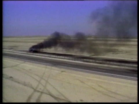 burning vehicle at side of road / basra, iraq - basra stock-videos und b-roll-filmmaterial