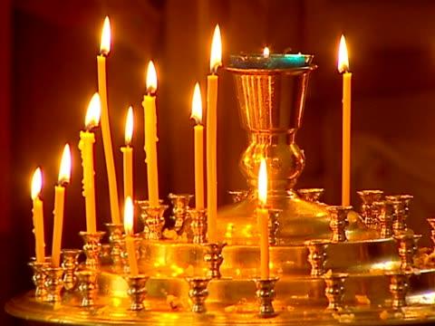 stockvideo's en b-roll-footage met burning wax candles during church ritual in a temple. - altaar