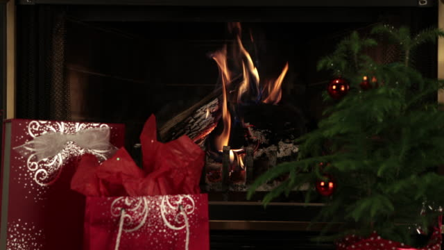 Burning Wood Inside Fireplace and Christmas Presents
