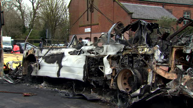 burnt out bus, removed from belfast street, after it was petrol bombed during riots and growing tensions in northern ireland - burnt stock videos & royalty-free footage