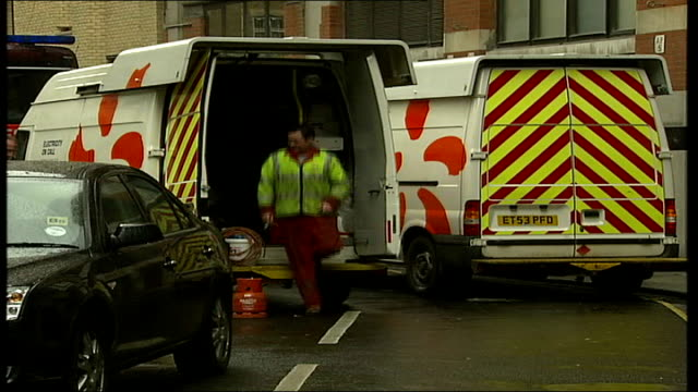 Burst water main in Holborn causes power cuts EXT Firefighters chatting in street Utility vans parked in street Water gushing down drain PULL OUT to...