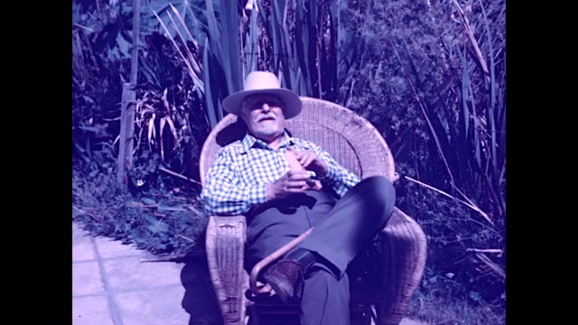 Burton Holmes who coined the phrase Travelogue sits in a wicker chair and cracks open a package of 16mm Kodachrome film Taken at the ranch home of...