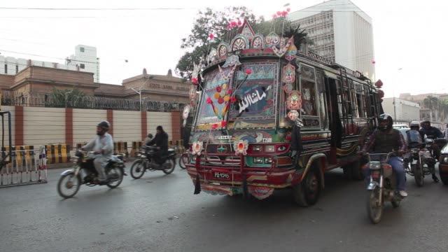 A bus and other traffic drive past the State Bank of Pakistan building in Karachi Pakistan on Thursday Dec 14 Pedestrians and an auto rickshaw drives...