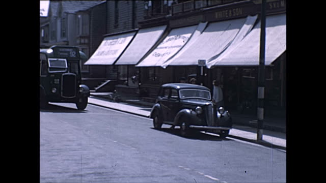 bus and standard flying 12 car outside shops / road views with pedestrians and ladies with push chairs / clarks shoe factory / street inn - 1950 stock videos & royalty-free footage