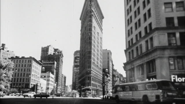 a bus approaches new york city's  flatiron building. - flatiron building manhattan stock videos and b-roll footage