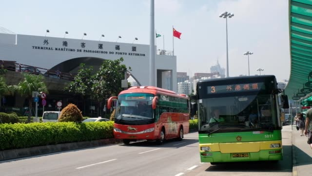 A bus arrives to drop passengers off at a stop near the Macau Outer Harbour Ferry Terminal in Macau China on Wednesday Sept 27 Tourists wait in line...