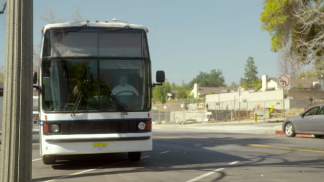 ts a bus bound for new york pulling up to a bus stop / sierra madre, california, united states - sierra madre stock-videos und b-roll-filmmaterial