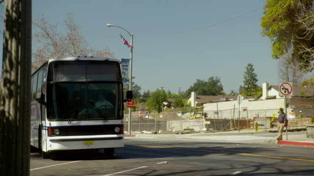 ms a bus bound for new york pulling up to a bus stop / sierra madre, california, united states - sierra madre stock-videos und b-roll-filmmaterial