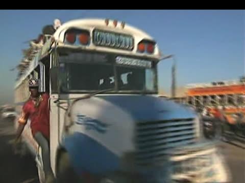 vídeos de stock e filmes b-roll de bus carrying large group of haitians drives through city of port au prince and towards neighbouring towns following devastating earthquake haiti 15... - hispaniola