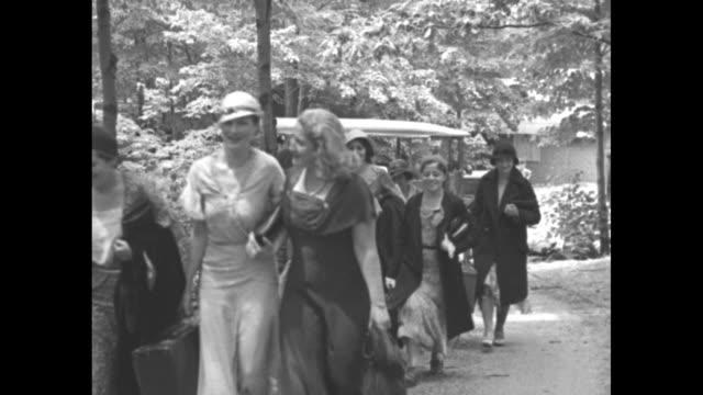 vídeos y material grabado en eventos de stock de bus carrying women pulls up at camp tera an unemployed women's camp at lake tiorati ny and women get off bus / women walking up pathway / women... - balancín