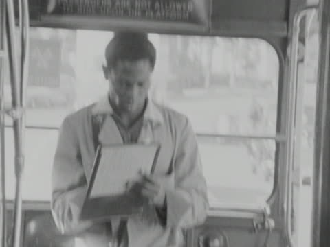 a bus conductor makes notes on his timetable - conductor stock videos and b-roll footage