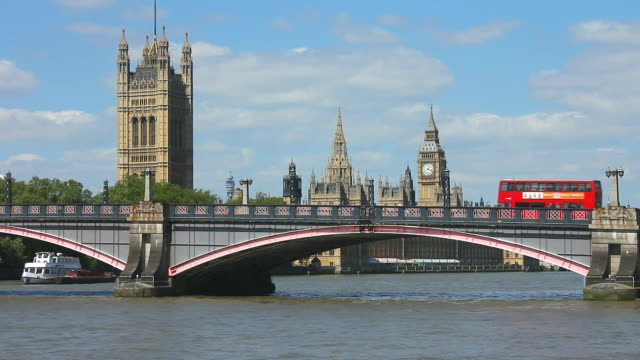bus crossing lambeth bridge with the houses of parliament in the background. - ウェストミンスター宮殿点の映像素材/bロール