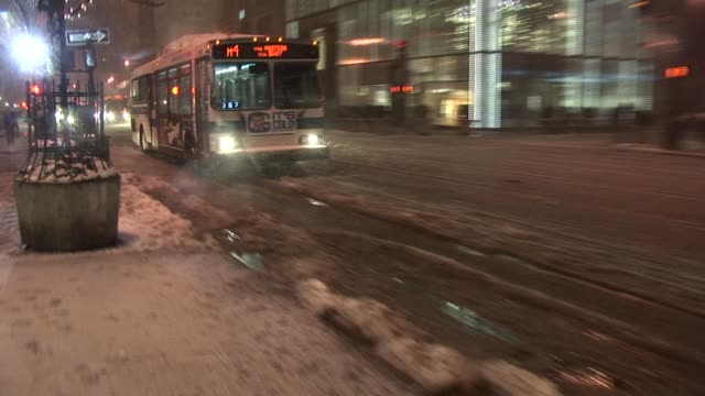 Bus dirves through slush in road splashing water onto sidewalk New York Available in HD