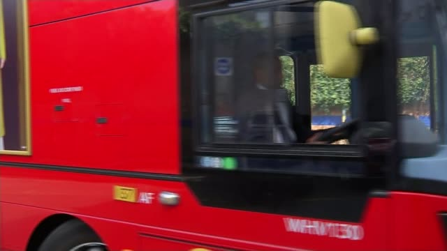 Bus driver hailed hero after woman pushed into road on Putney Bridge by jogger Reporter to camera Double decker red London bus towards into bus...