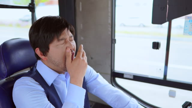 a bus driver yawns in the bus - bus driver stock videos & royalty-free footage