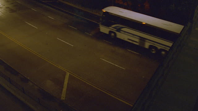 a bus drives on a freeway at night. - bus stock videos & royalty-free footage
