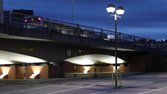 bus on a concrete bridge passing over a deserted car park at twilight with street lights in foreground - ominous stock videos & royalty-free footage