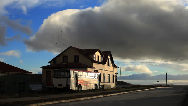 ms bus parked next to house in sunset light / porvenir, chilean patagonia, chile - travelling light stock videos & royalty-free footage