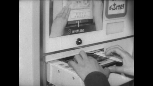 bus passengers in japan make their way to railroad station / man puts paper money into an automated ticket machine / coin drops out of bottom / man... - 自動改札機点の映像素材/bロール